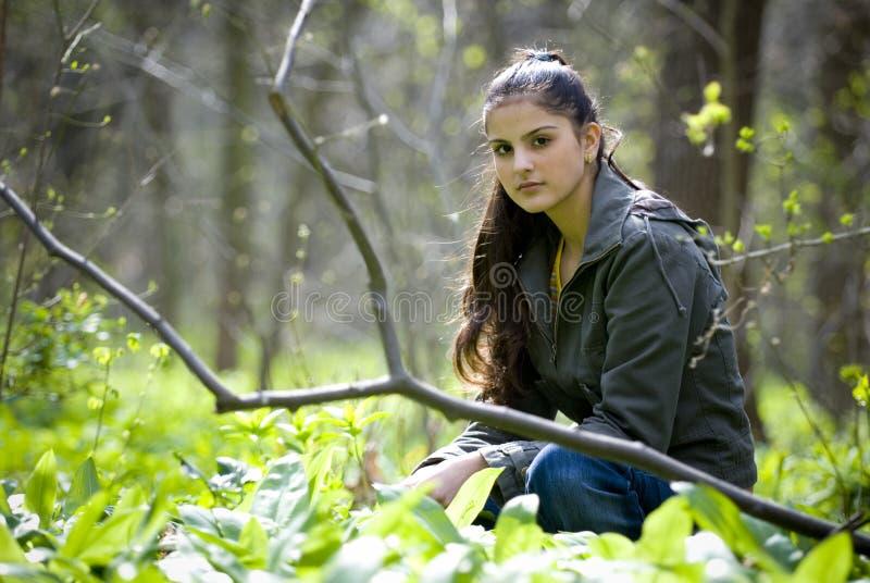 Donna graziosa che si siede nella foresta fotografie stock