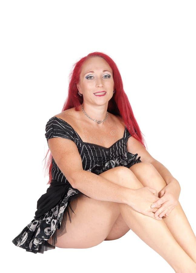 Donna graziosa che si siede sul pavimento fotografie stock