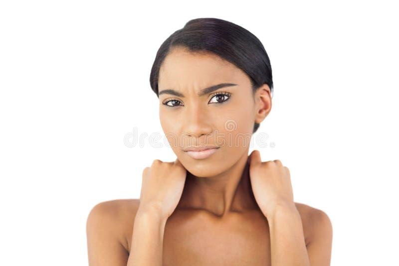 Donna graziosa che soffre dal collo doloroso immagine stock