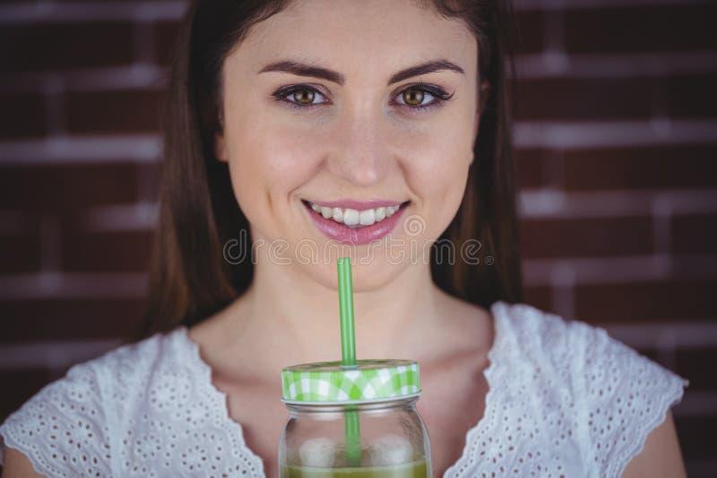 Donna graziosa che sorseggia sul succo verde fotografie stock