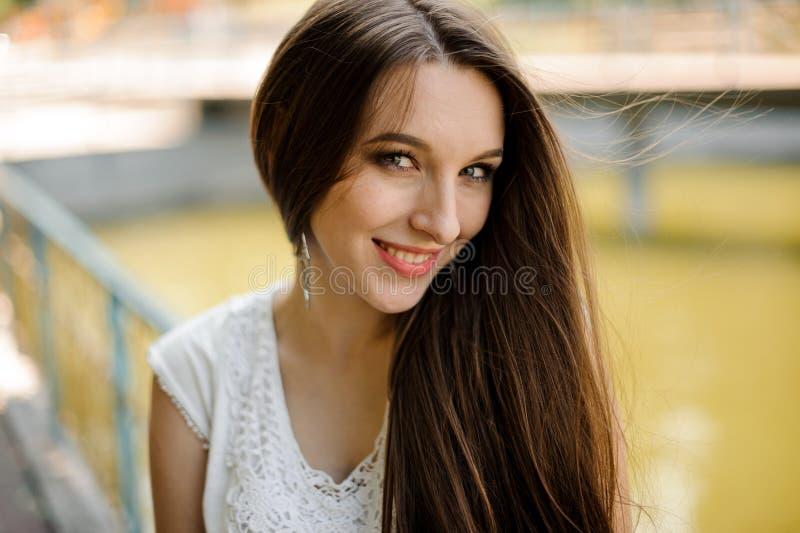 Donna graziosa con capelli scuri in vestito bianco elegante immagini stock libere da diritti