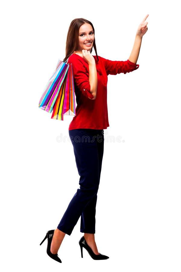 Donna graziosa con i sacchetti della spesa che mostrano su qualcosa sopra fotografia stock libera da diritti