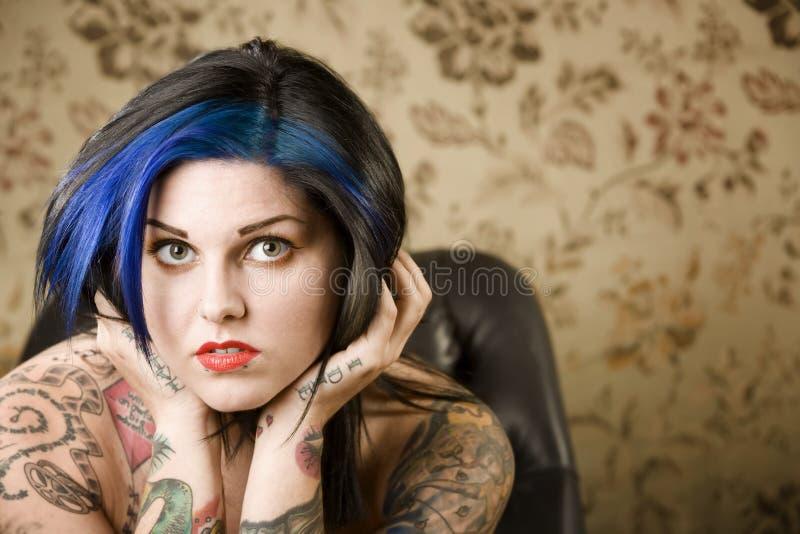 Donna graziosa con i tatuaggi in una sedia di cuoio fotografia stock libera da diritti
