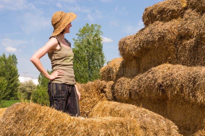 Donna graziosa con il cappello che sta con le mani sulla sua vita vicino alle balle della paglia immagini stock
