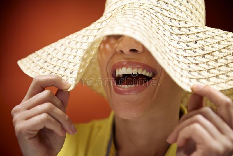 Donna graziosa con il cappello di paglia che sorride e che si diverte immagini stock
