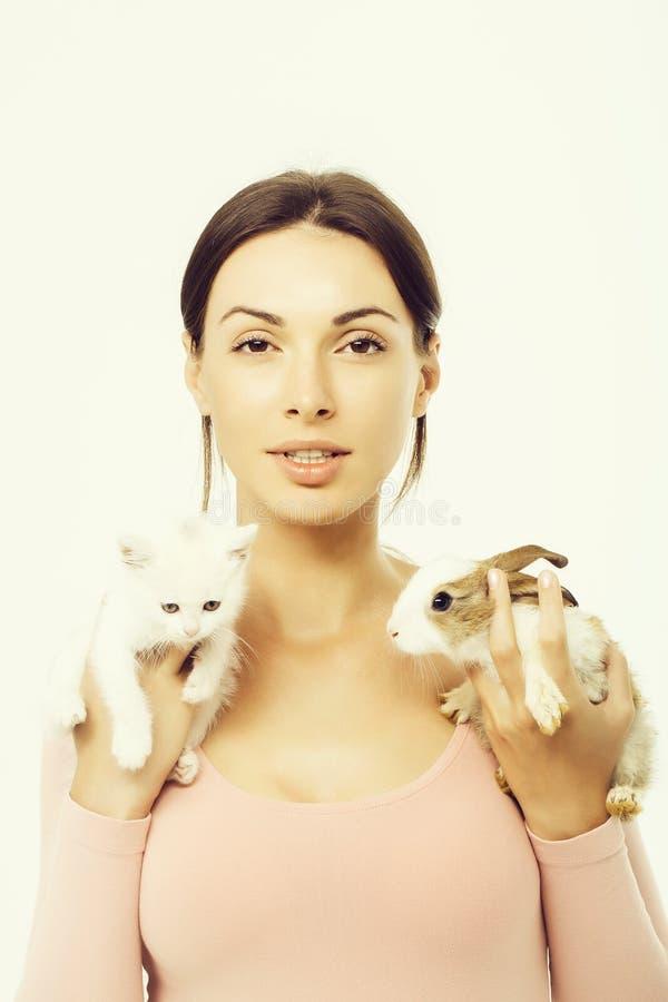 Donna graziosa con il gattino ed il coniglio isolati immagine stock