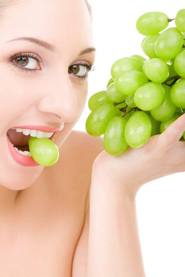 Donna graziosa con l'uva verde immagini stock libere da diritti