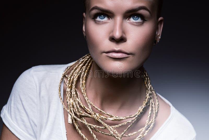 Donna graziosa con la collana della corda dell'oro fotografia stock