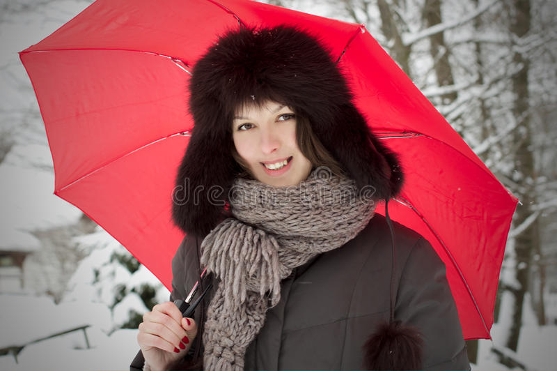 Donna graziosa con lo sguardo dell'ombrello nella neve di inverno fotografie stock libere da diritti