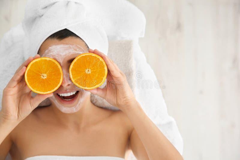 Donna graziosa con ringiovanire maschera facciale che tiene arancia affettata nel salone della stazione termale immagine stock libera da diritti