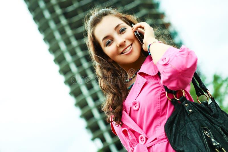 Donna graziosa con un cellulare fotografia stock libera da diritti