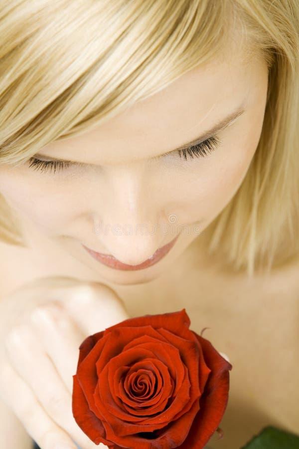 Donna graziosa con un fiore fotografia stock libera da diritti