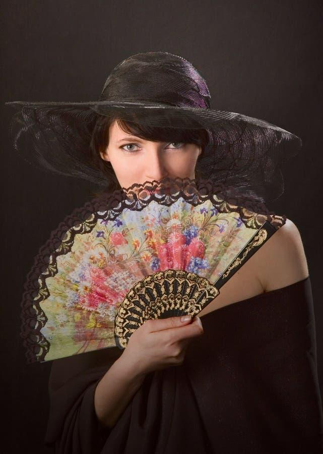 Donna graziosa con un ventilatore immagini stock
