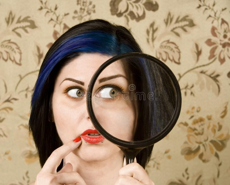 Donna graziosa con una lente d'ingrandimento immagine stock libera da diritti