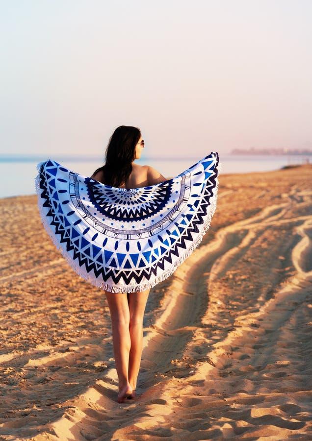 Donna graziosa con una tappezzeria rotonda della spiaggia della mandala nell'oceano co immagini stock