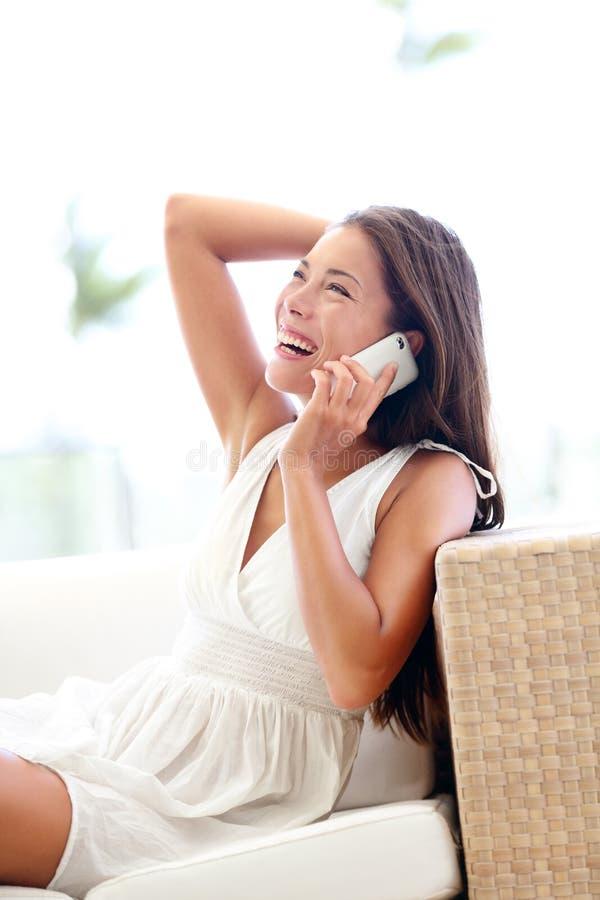 Donna graziosa dello Smart Phone che parla seduta allegra fotografie stock