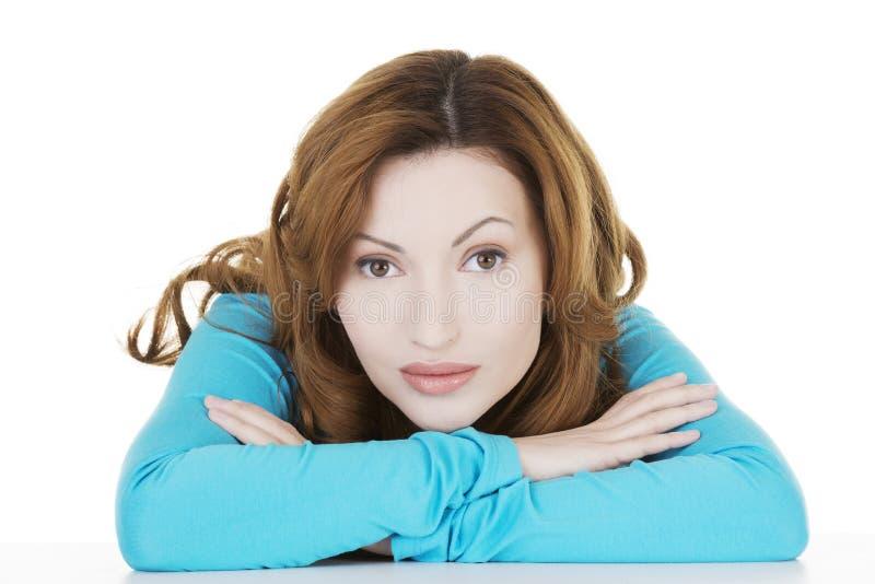 Donna graziosa e felice in abbigliamento casual che si siede allo scrittorio fotografia stock