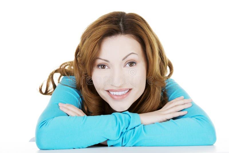 Donna graziosa e felice in abbigliamento casual che si siede allo scrittorio immagine stock libera da diritti