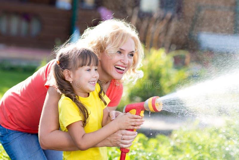 Donna graziosa e sua la figlia che innaffiano con il tubo flessibile nel giardino fotografie stock libere da diritti