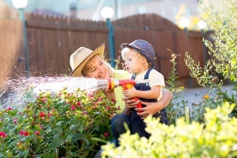 Donna graziosa ed i suoi fiori d'innaffiatura del figlio con il tubo flessibile dell'acqua nell'iarda immagine stock