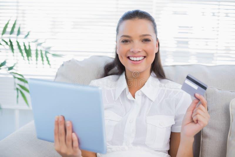 Donna graziosa felice che compra online facendo uso del suo pc della compressa immagine stock