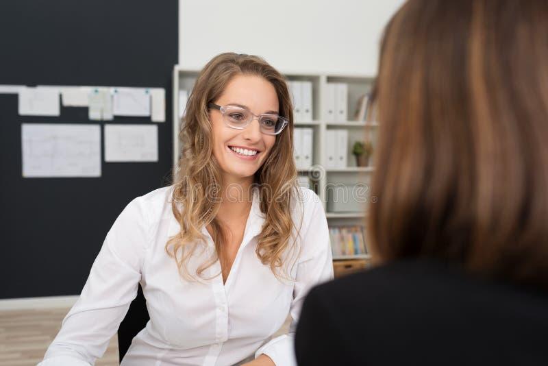 Donna graziosa felice dell'ufficio che parla con Ufficio-compagno fotografia stock libera da diritti