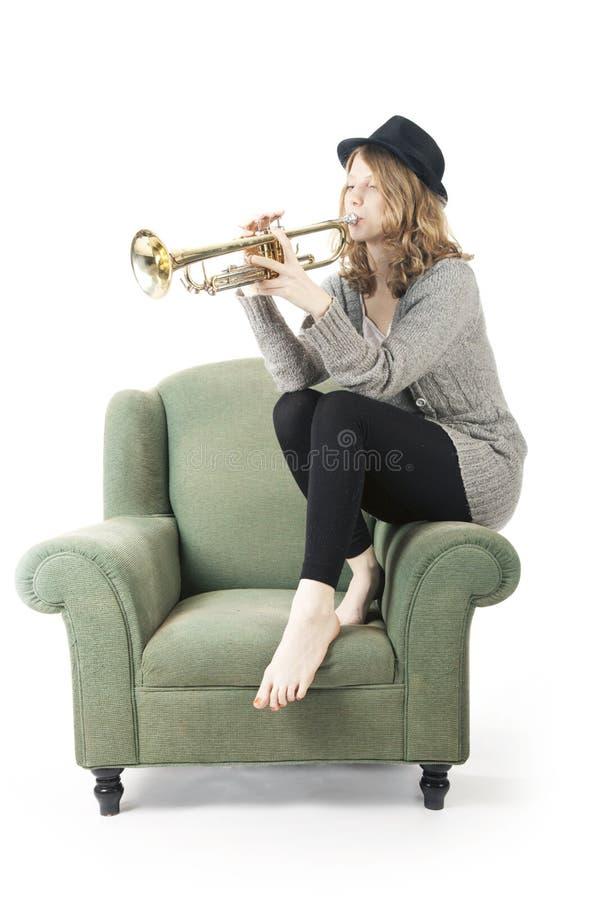 Donna graziosa giovane che gioca la tromba che si siede sulla poltrona fotografia stock libera da diritti