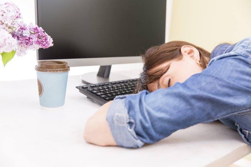 Donna graziosa giovane stanca ed esaurita di lavoro che si trova sulla tavola davanti al computer e che prende una rottura immagini stock libere da diritti
