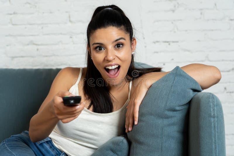 Donna graziosa latina felice a casa guardando la televisione fotografia stock