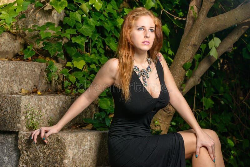 Donna graziosa messa sulle scale fotografie stock libere da diritti