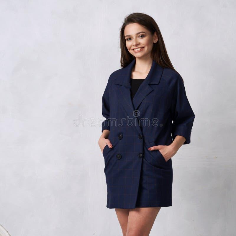 Donna graziosa in mini vestito blu con quattro bottoni fotografia stock