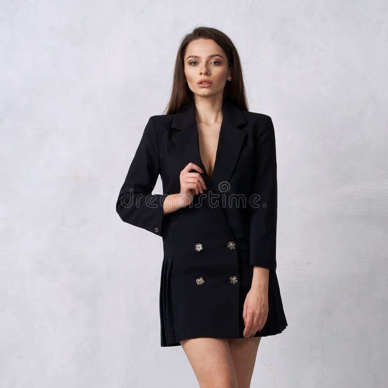 Donna graziosa in mini vestito nero con quattro bottoni fotografia stock