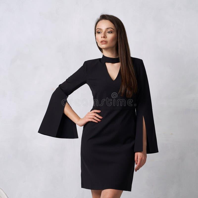 Donna graziosa in mini vestito nero con quattro bottoni immagini stock