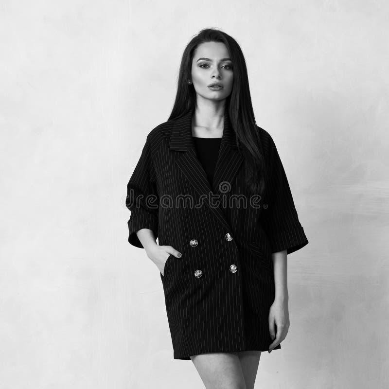 Donna graziosa in mini vestito nero con quattro bottoni immagini stock libere da diritti