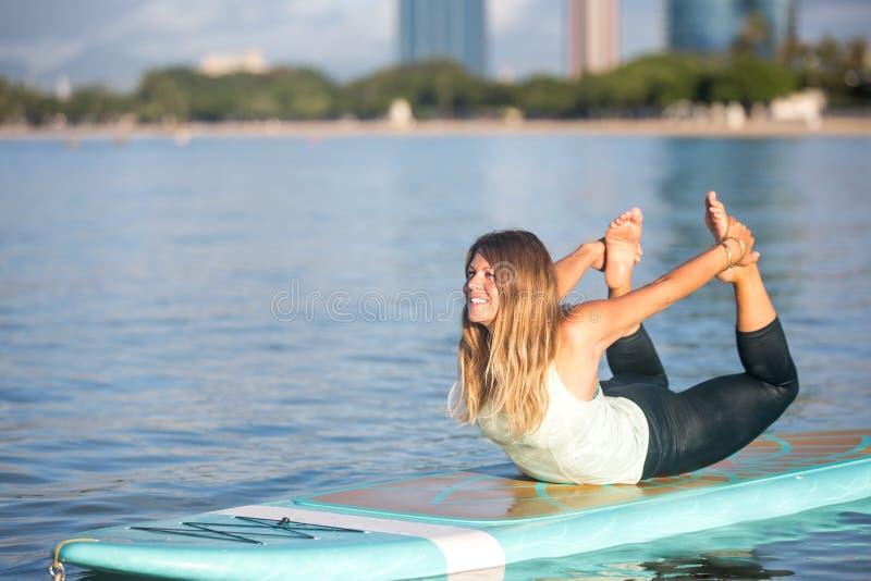 Donna graziosa nella posa dell'arco che fa yoga del SUP sull'acqua immagini stock