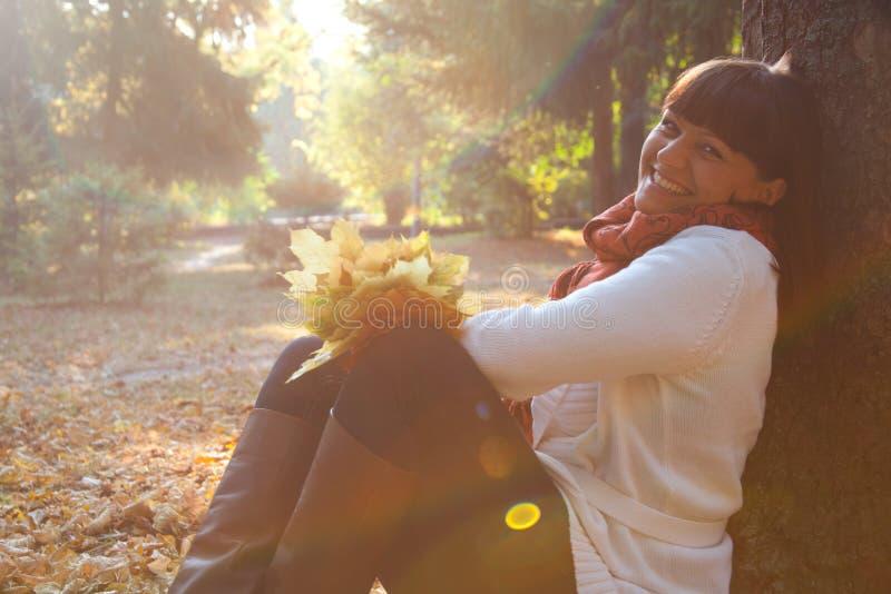 Donna graziosa nella sosta di autunno fotografia stock libera da diritti