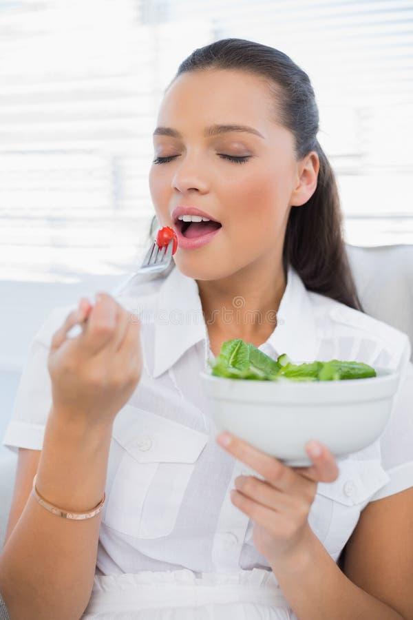 Donna graziosa pacifica che mangia insalata sana che si siede sul sofà immagine stock
