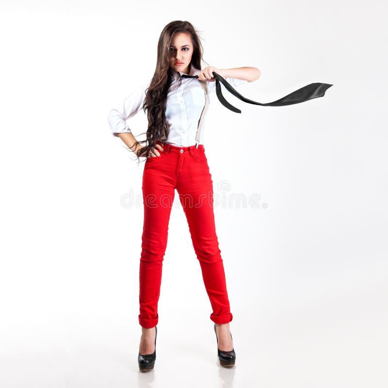 Donna graziosa in pantaloni e foulard rossi di volo in studio fotografia stock