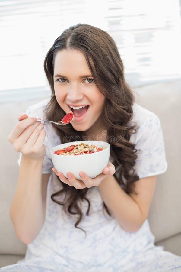 Donna graziosa in pigiami che mangia cereale fruttato immagini stock libere da diritti