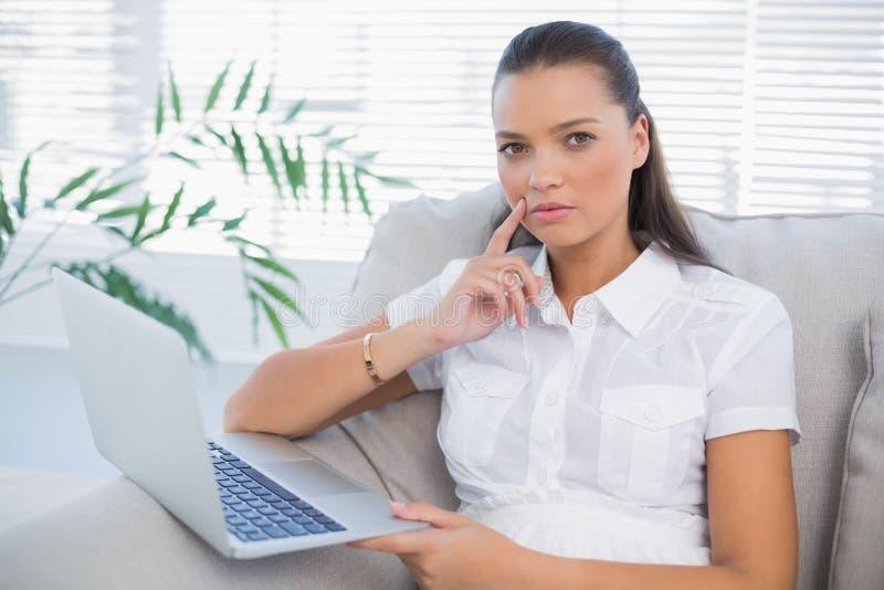 Donna graziosa premurosa che per mezzo del computer portatile che si siede sul sofà accogliente fotografie stock libere da diritti