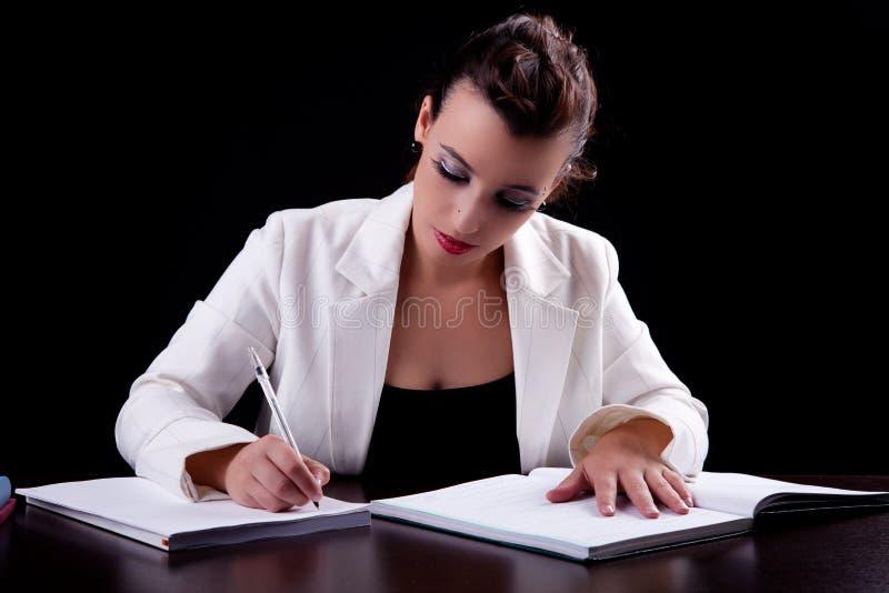 Donna graziosa in scrittorio con i documenti, scriventi fotografia stock libera da diritti
