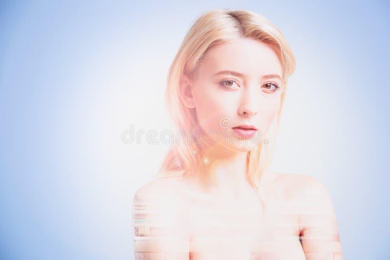 Donna graziosa seria che sta contro il fondo blu fotografie stock