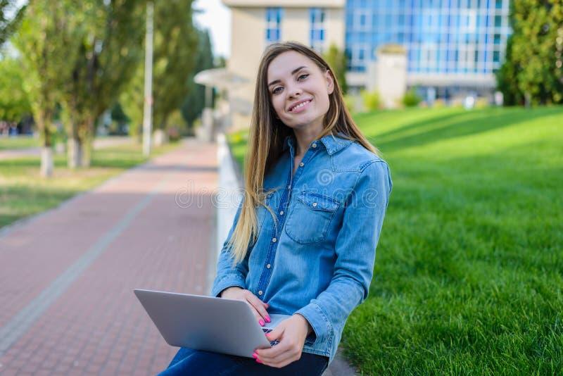 Donna graziosa sorridente in abbigliamento casual con il computer portatile sulle sue gambe i fotografia stock libera da diritti