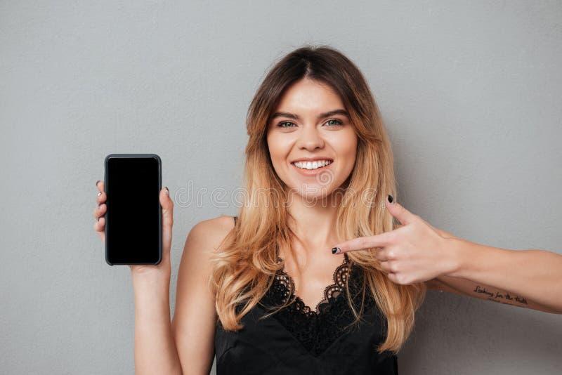 Donna graziosa sorridente che indica dito al telefono cellulare dello schermo in bianco fotografie stock