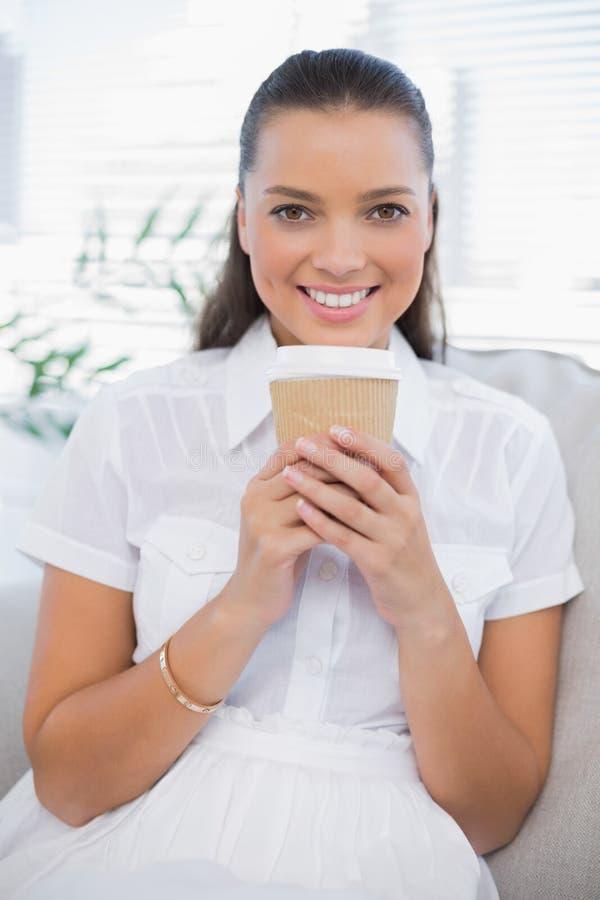 Donna graziosa sorridente che mangia caffè che si siede sullo strato accogliente fotografia stock libera da diritti