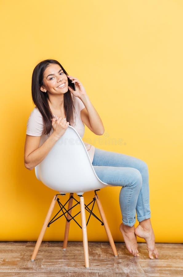 Donna graziosa sorridente che parla sul telefono fotografie stock