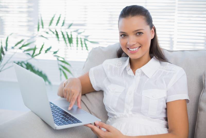 Donna graziosa sorridente che per mezzo del computer portatile che si siede sul sofà accogliente fotografia stock libera da diritti