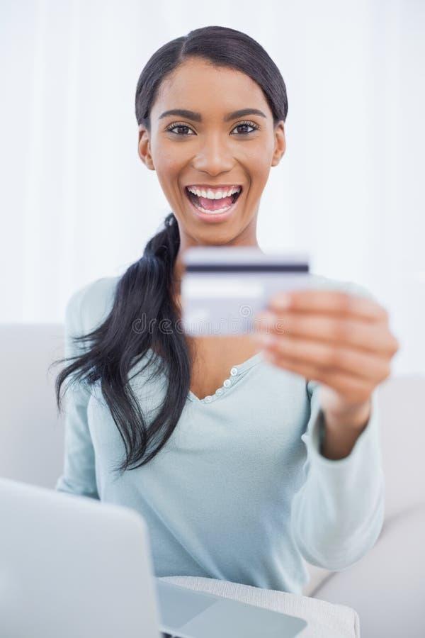 Donna graziosa sorridente che per mezzo del suo computer portatile per comprare online immagini stock