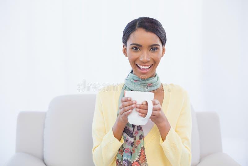 Donna graziosa sorridente che si siede sulla tazza della tenuta del sofà di caffè immagine stock libera da diritti