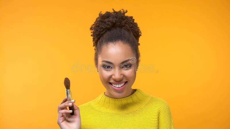 Donna graziosa sorridente con la spazzola di trucco che guarda in camera sul fondo giallo immagine stock